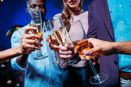 Photo for Cropped shot of young multiethnic people clinking glasses of champagne at new year party - Royalty Free Image