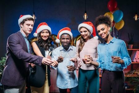 Photo pour Heureux jeunes amis multiethniques célébrant le nouvel an avec champagne et feux de Bengale - image libre de droit