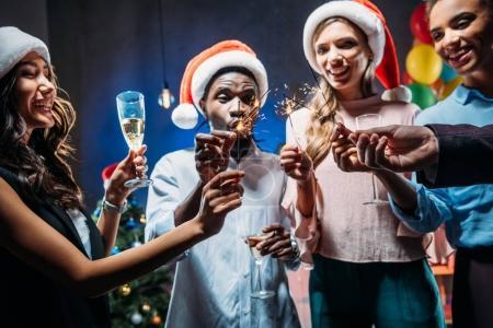 Photo pour Heureux jeunes amis multiethniques dans chapeaux Santa célébrer la nouvelle année avec des étincelles et du champagne - image libre de droit