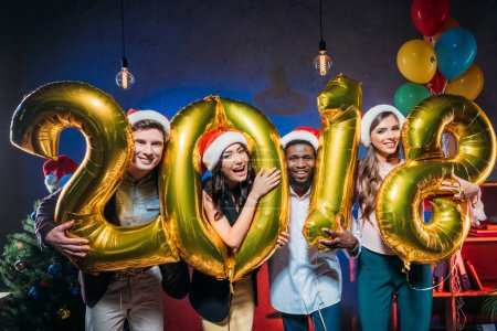 Photo for Happy young friends holding golden 2018 sign balloons and smiling at camera - Royalty Free Image