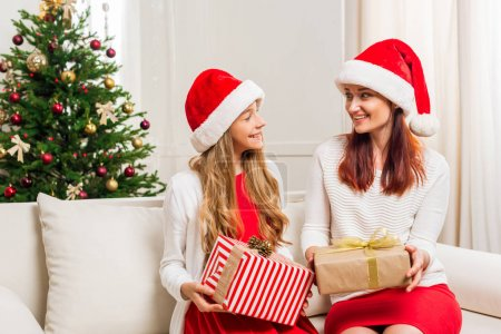 Photo for Happy beautiful mother and daughter with christmas gifts sitting on sofa - Royalty Free Image