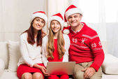 family in santa hats with laptop