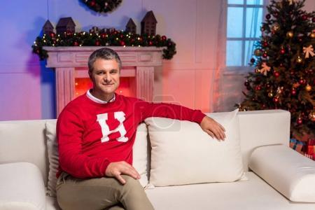 Mature man sitting on sofa on christmas