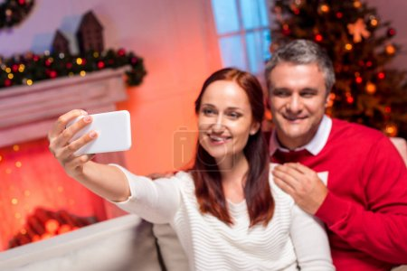 couple taking selfie with christmas tree