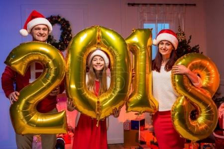 Happy family with new year balloons