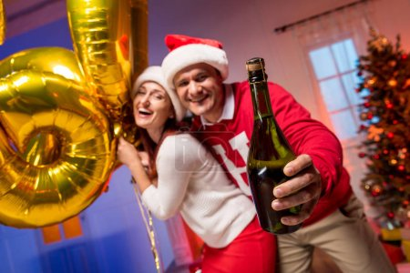Couple with balloons and champagne bottle