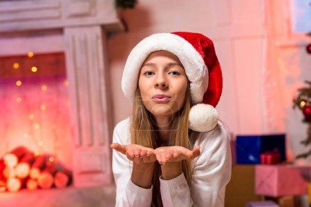 Photo for Beautiful teen girl in santa hat sending kiss - Royalty Free Image