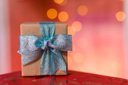 Photo for Small gift box with blue glossy bow on red table - Royalty Free Image