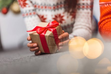 Photo for Close-up partial view of young woman holding christmas present - Royalty Free Image