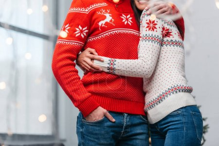 Photo for Cropped shot of young couple in warm knitted sweaters hugging indoors - Royalty Free Image
