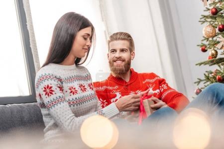man presenting christmas gift to girlfriend