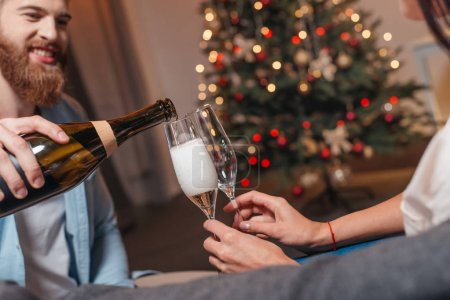 Photo for Handsome young man pouring champagne into glasses while celebrating new year with girlfriend - Royalty Free Image