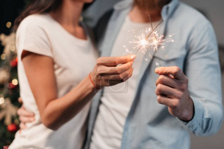 Photo for Cropped shot of young couple holding sparklers at new year party - Royalty Free Image