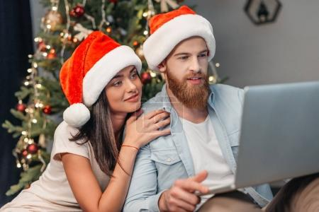 couple using laptop at christmas eve