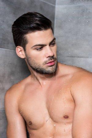 Photo pour Beau jeune homme réfléchi prenant une douche - image libre de droit