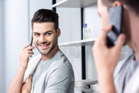 man talking by phone in bathroom