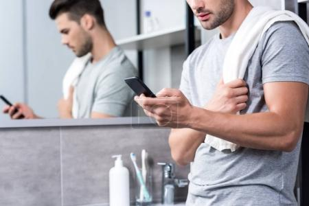 man using smartphone in bathroom