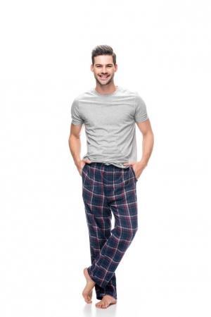Photo pour Beau jeune homme en pyjama avec les mains dans les poches isolés sur blanc - image libre de droit