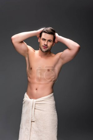Photo pour Handsome young man covering with towel after shower - image libre de droit