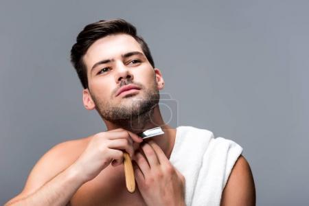 man shaving with straight razor