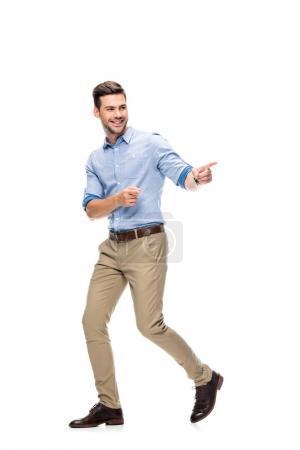 Photo pour Bel homme marchant et pointant sur le côté isolé sur blanc - image libre de droit