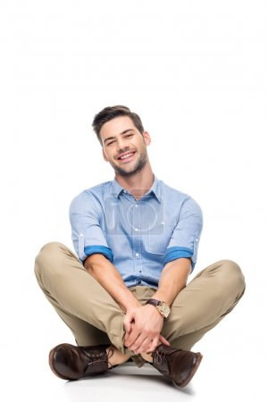 Photo for Happy young man sitting on floor with crossed legs isolated on white - Royalty Free Image