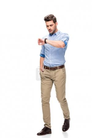 Photo for Handsome man walking and looking at watch isolated on white - Royalty Free Image