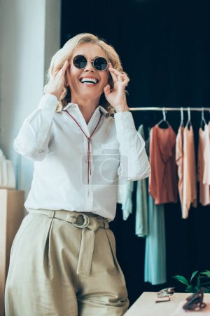 Photo pour Portrait de femme élégante portant des lunettes de soleil lors de vos achats dans la boutique de vêtements - image libre de droit