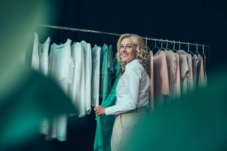 smiling woman choosing clothes in store