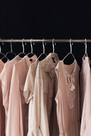 Photo for Close up view of arranged feminine clothing hanging on clothes rack isolated on black - Royalty Free Image