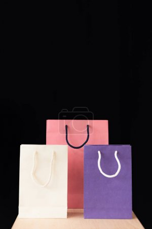 Photo for Various shopping bags on wooden tabletop isolated on black - Royalty Free Image