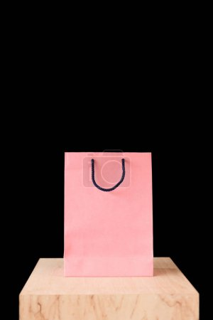 Photo pour Sac à provisions rose sur le dessus de table en bois isolé sur fond noir - image libre de droit
