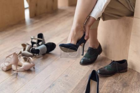 Photo for Partial view of woman wearing shoe while shopping in clothing boutique - Royalty Free Image