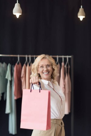 woman with shopping bags in clothing store
