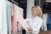 woman choosing clothes in clothing store