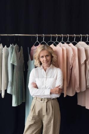 Photo for Portrait of stylish woman with arms crossed looking at camera while standing in clothing store - Royalty Free Image