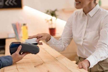 Photo for Partial view of smiling woman making payment with credit card in cafe - Royalty Free Image