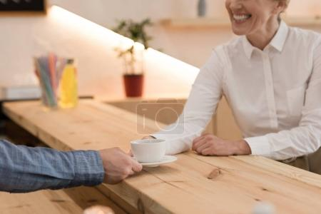 barista giving order to woman