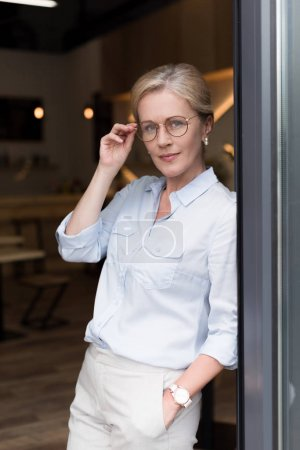 Photo for Portrait of pensive stylish woman in eyeglasses with hand in pocket looking at camera - Royalty Free Image
