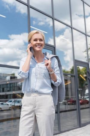 smiling woman talking by phone