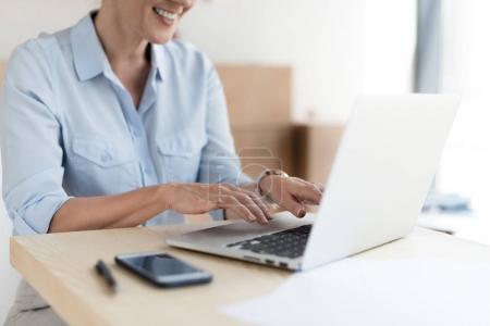 Photo pour Plan recadré de souriante femme d'affaires mature en utilisant un ordinateur portable - image libre de droit