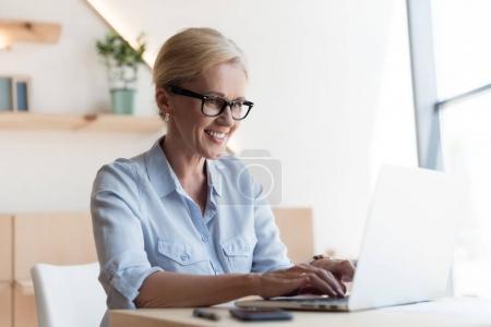 Photo pour Souriant mature femme d'affaires dans les lunettes à l'aide d'un ordinateur portable - image libre de droit