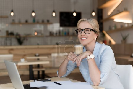 Photo for Smiling mature businesswoman in eyeglasses drinking coffee while working in cafe - Royalty Free Image