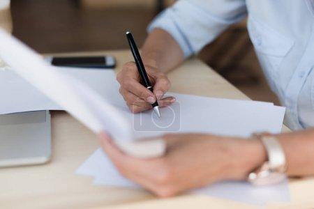 Photo pour Gros plan vue partielle de femme d'affaires écrivant tout en travaillant avec des documents - image libre de droit