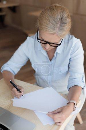 Photo pour Vue d'angle élevé de mature femme d'affaires en travaillant avec des papiers de lunettes de vue - image libre de droit