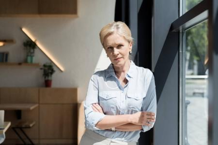 Photo pour Confident serious mature woman standing with crossed arms and looking at camera - image libre de droit