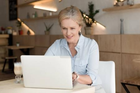 Photo for Smiling mature woman using laptop while working in cafe - Royalty Free Image