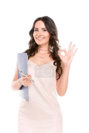 Photo for Beautiful young woman holding clipboard and showing ok sign isolated on white - Royalty Free Image