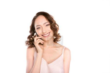 Photo pour Jeune femme asiatique gaie parler sur smartphone et souriant à la caméra isolé sur blanc - image libre de droit