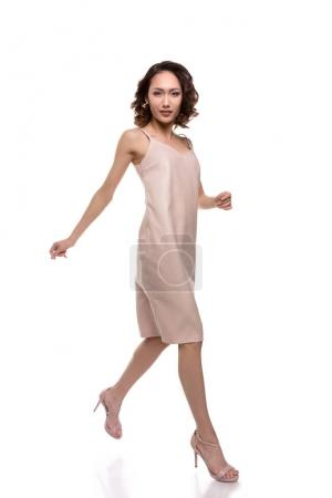 Photo for Gorgeous young asian woman in pink dress walking and looking at camera isolated on white - Royalty Free Image